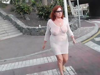 Marvelous older wench walks around the town with exposed love melons